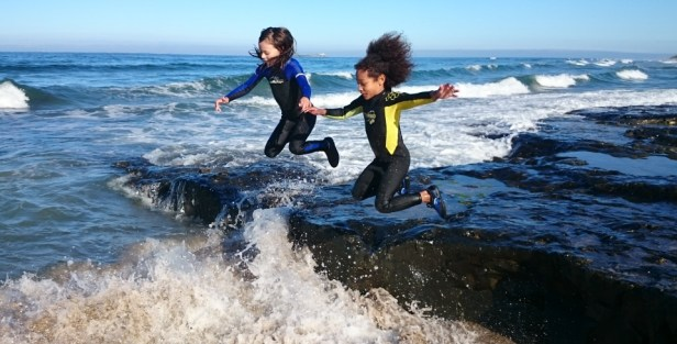 Image of girls-in-wetsuits-leaping-from-rocks-into-foaming-sea