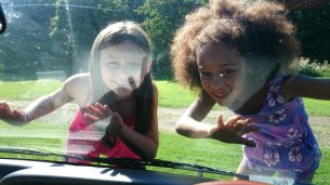 Image of girls-standing-on-vehicle-front-bumper-looking-in