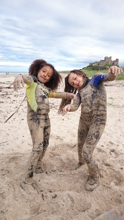 Image of two-girls-in-westuits-covered-in-sand-being-zombies-on-the-beach-with-castle-in-background