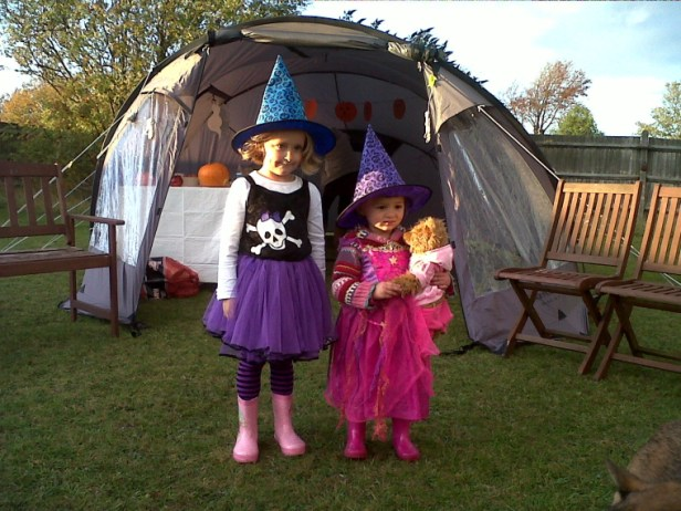 two-girls-in-witches-costumes-outside-tent-in-back-garden