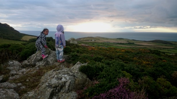 two-girls-on-rocks-overlooking-the-sea-at-sunset