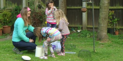 Image of woman-and-girls-filling-bird-feeders-in-garden