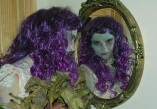 Image of woman-looking-in-mirror-with-purple-wig-halloween-fancy-dress