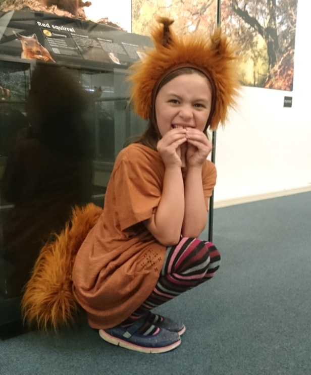 girl-dressed-in-red-squirrel-outfit-crouching-indoors