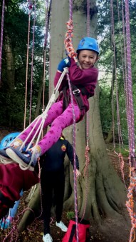 Image of girl-in-standing-position-in-climbing-harness