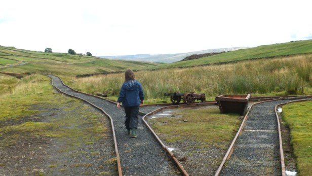 girl walking on disused railway-tracks with hills in distance