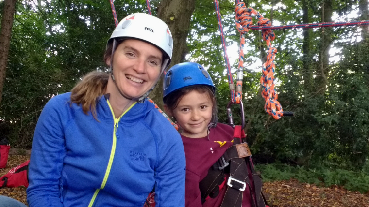 Image woman-and-girl-in-helmets-with-climbing-harness-near-tree