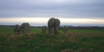 Image of bronze age duddo-stone-circle-of-5-stones-standing-on-a-hill-with-mountains-in-background