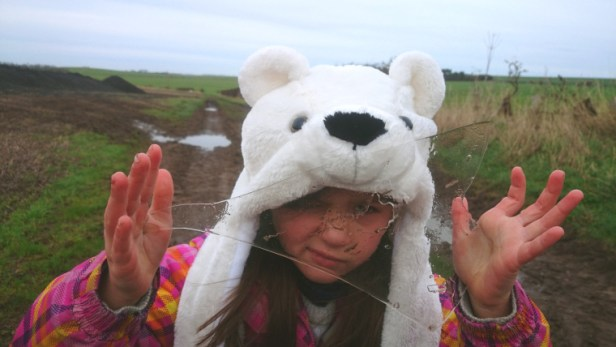 young-girl-in-polar-bear-hat-holding-up-piece-of-broken-ice-in-a-field
