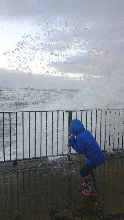 23girl-in-blue-coat-being-soaked-by-giant-wave-over-sea-wall-railings