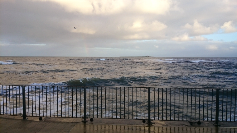 Image of brooding-sea-with-pale-rainbow-on-horizon-next-to-island-railings-in-foreground