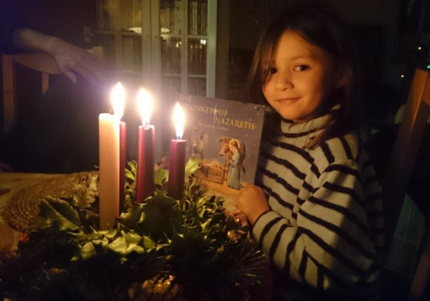 child-with-book-behind-candlelit-evergreen-advent-wreath