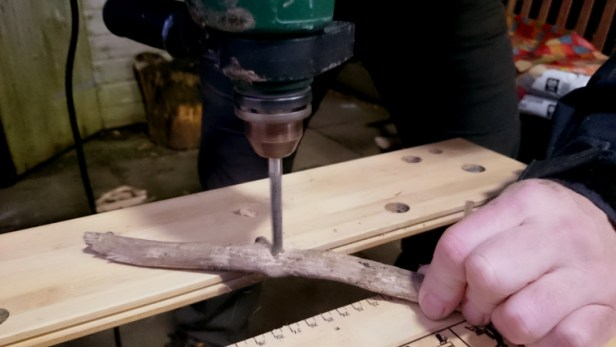 Image close-up-of-hands-and-drill-on-work-bench-making-hole-in-driftwood-stick
