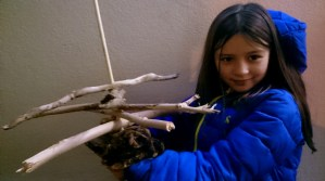 Image of girl-in-blue-jacket-holding-out-driftwood-sticks-attached-to-dowling-rod