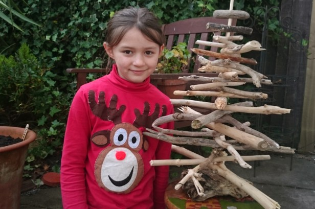 girl-in-red-reindeer-jumper-next-to-driftwood-christmas-tree-in-a-garden