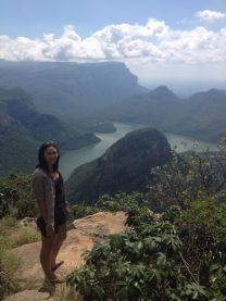 Image of woman standing on rock with stunning lake and mountain valley view