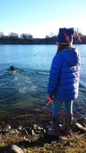 Image of girl-in-blue-coat-by-quarry-lake-with-black-dog-swimming