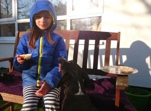 Image of girl-in-blue-coat-on-bench-with-dog