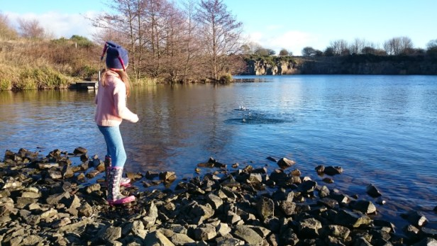 girl-in-pink-jumper-blue-leggings-and-woolly-hat-skimming-stone-on-quarry-lake