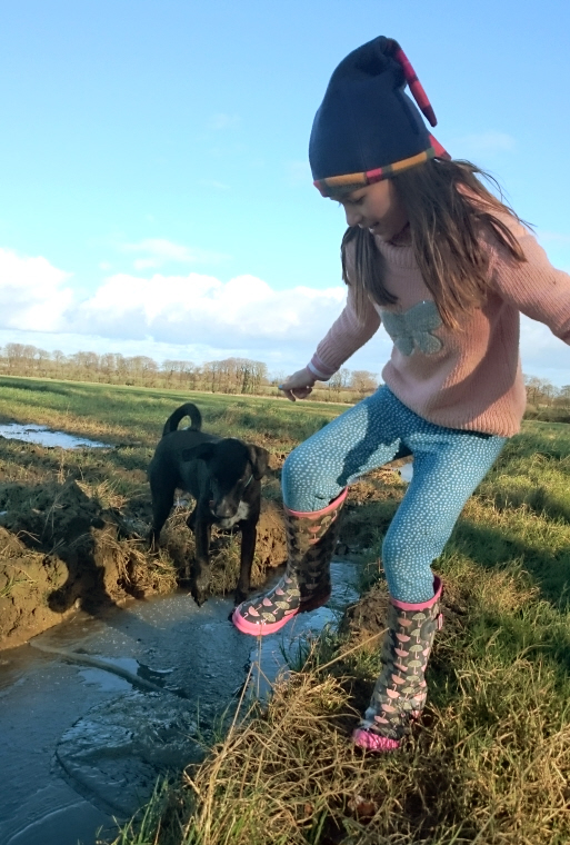 Image of girl-with-dog-jumping-on-frozen-puddles-in-tractor-tracks