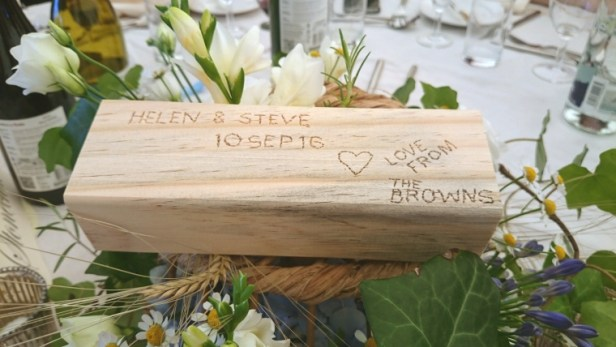 jenga-block-with-engraved-writing-on-wedding-table-with-flowers