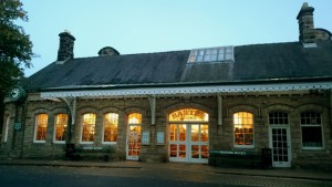 Image of old Victorian style railway station building with windows lit at twilight and Barter Books written above door