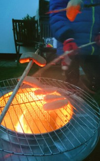 close-up image -of-sausages-cooking-on-firepit-in-washing-machine-drum