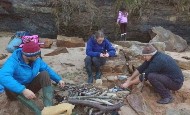men-woman-and-girl-sorting-sticks-for-campfire-in-sand