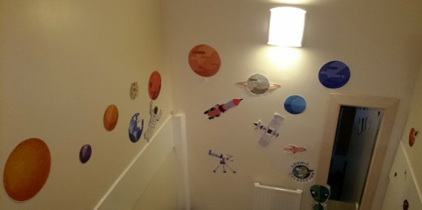 pictures-of-planets-etc-stuck-to-wall-of-stairwell