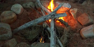 Image of tipi-of-sticks-campfire-in-circle-of-rocks