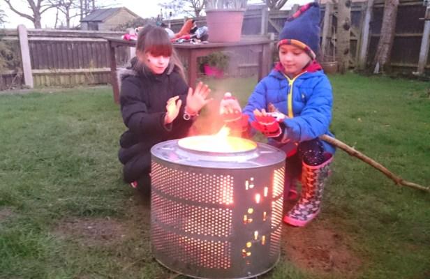 two-girls-warming-hands-next-to-fire-in-washing-machine-drum-in-garden