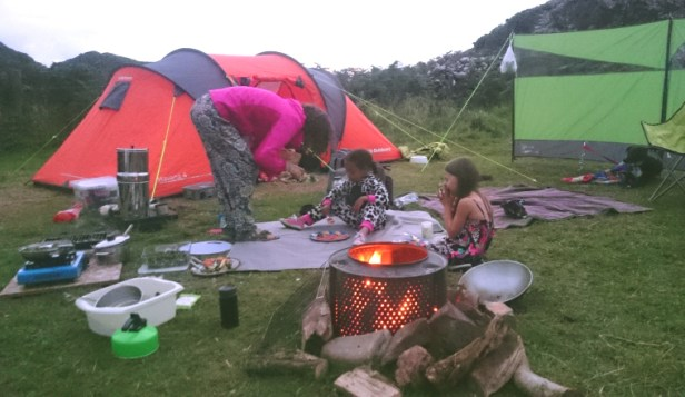 woman-and-girls-in-front-of-tent-and-windbreak-with-metal-drum-firepit-in-foreground