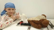 Image of girl in blue bandana with thumbs up next to teddy bear in medical mask