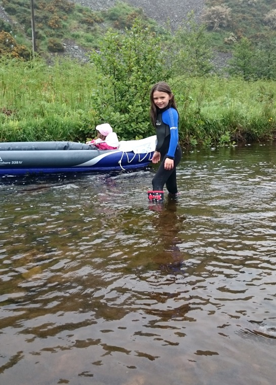 Image of girl in wetsuit paddling in river with inflatable canoe