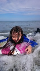 Image of girl on bodyboard with white water in sea close up