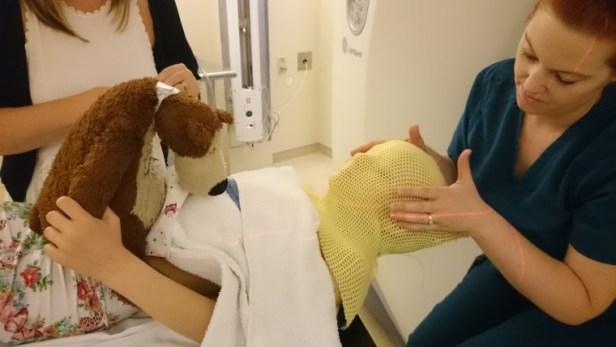 Girl with teddy having thermoplastic mask fitted by 2 nurses