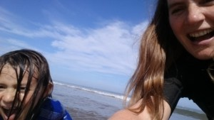 Image of selfie of woman and child with sea and sky in background