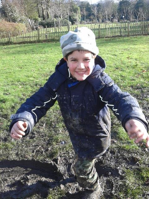 Image of boy in field covered in mud