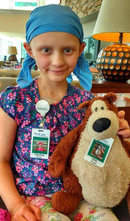 Image of girl with no hair in bandana with teddy bear, both with ID badges