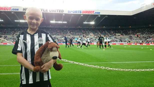 Girl with no hair wearing Newcastle football kit carrying brown and cream bear on pitch in stadium