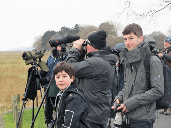 Group of people watching birds with cameras and binoculars