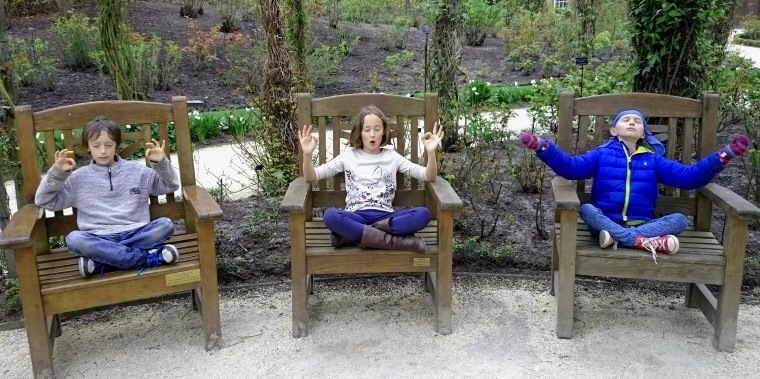 Image of three children each sitting on wooden seat in garden in meditation pose
