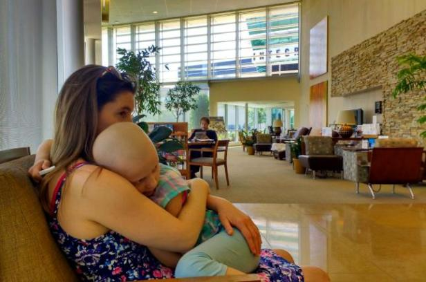 Woman cuddling child on chair in waiting room