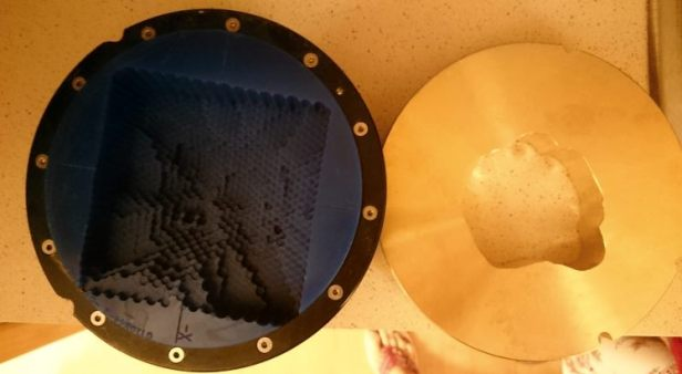 Blue circular mould with lego-like 3D depth cutout, and brass circular mould with 2D tumour-shaped cutout