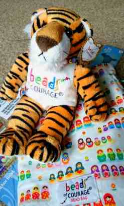 Image of cuddly toy tiger and coloured cloth bag with Beads of Courage logos