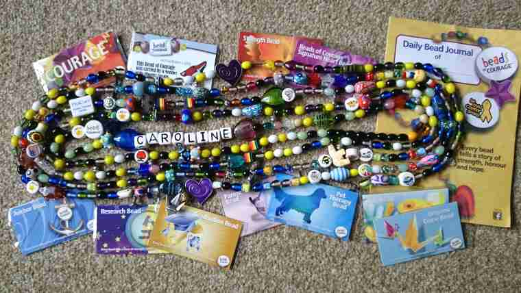 Image of string of multicoloured beads in spiral with Beads of Courage information cards
