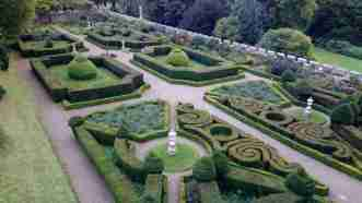 Image of bird's eye view of box hedge Tudor style knot garden with castellated wall around