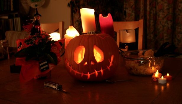 Image of carved pumpkin, witch doll, candles and bowl of pumpkin guts on table in house