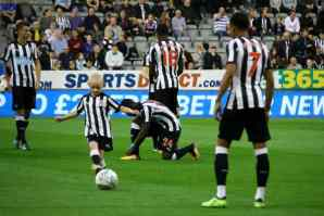 Image of football players on pitch in black and white kit kicking ball with female mascot