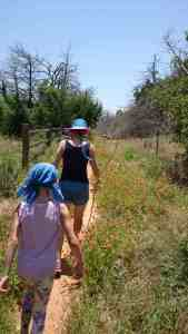Image of girl in bandana and woman in sun hat hiking through meadow flowers in sunshine